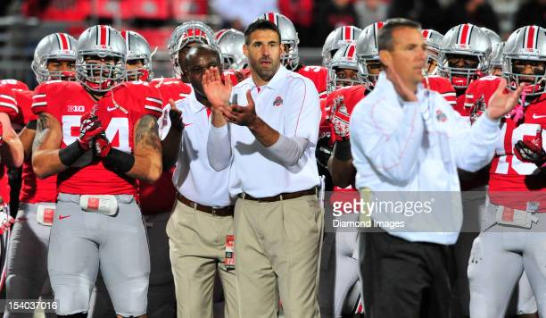 Linebackers coach Mike Vrabel and defensive coordinator Everett Withers of the Ohio State Buckeyes clap on the field during pregame warm ups before a...