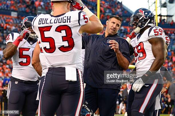 Linebackers coach Mike Vrabel of the Houston Texans works with Texans players before a game against the Denver Broncos at Sports Authority Field at...
