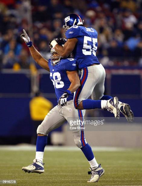 Linebackers Dhani Jones and Mike Barrow of the New York Giants celebrate on the field during the game against the Carolina Panthers on December 28...