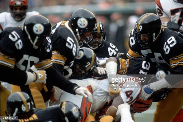 Linebackers Jack Ham, Jack Lambert and Robin Cole and defensive backs Donnie Shell, J.T. Thomas and Dwayne Woodruff of the Pittsburgh Steelers tackle...