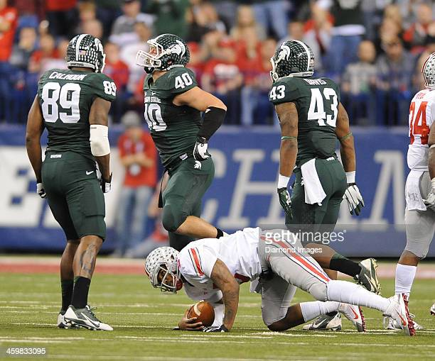 Linebackers Max Bullough, Ed Davis, and Shilique Calhoun of the Michigan State Spartans celebrate after a sack of quarterback Braxton Miller of the...