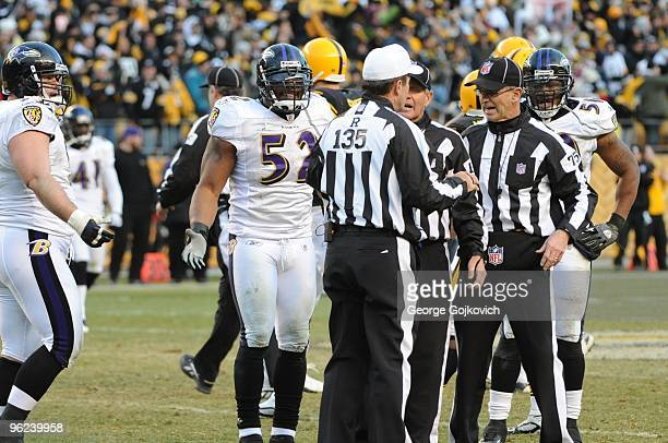 Linebackers Ray Lewis and Antwan Barnes of the Baltimore Ravens watch as referee Pete Morelli discusses an official's call with side judge Laird...