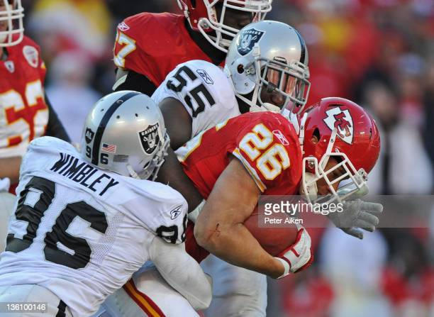 Linebackers Rolando McClain and Kamerion Wimbley of the Oakland Raiders tackle running back Jackie Battle of the Kansas City Chiefs after a short...