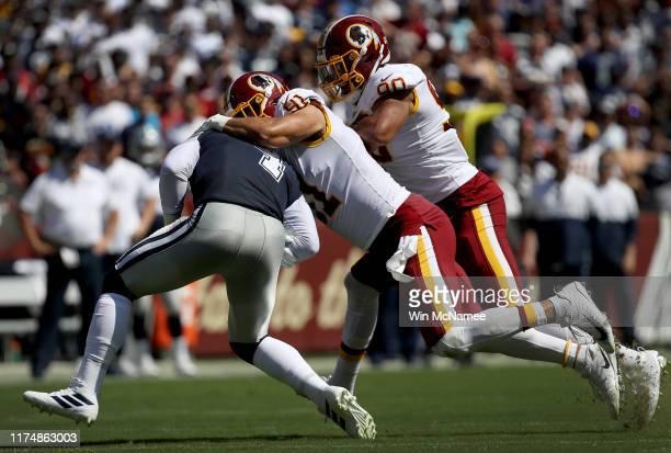 Linebackers Ryan Kerrigan and Montez Sweat of the Washington Redskins sack quarterback Dak Prescott of the Dallas Cowboys in first half action at...