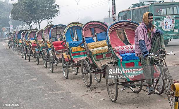 Lined up RICKSHAWS in north DHAKA during IJTEMA. Hundreds of thousands of Rickshaw Wallahs earn a living driving these.