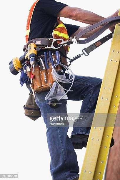 Lineman climbing a ladder