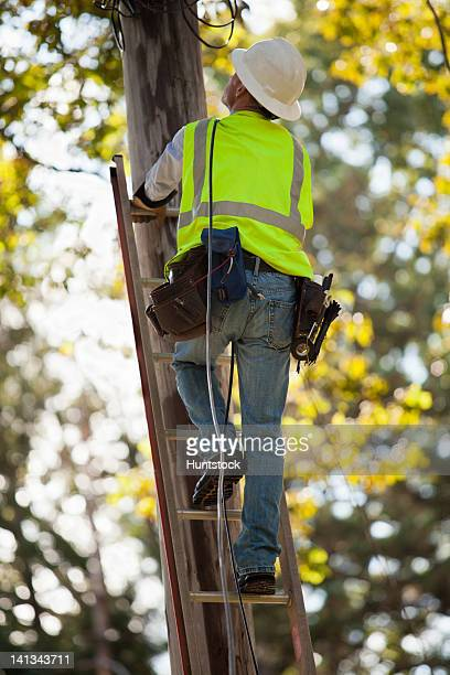 Lineman climbing utility pole to work on wires