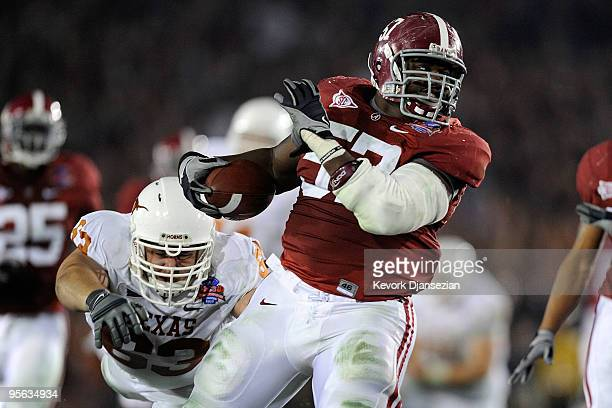 Lineman Marcell Dareus of the Alabama Crimson Tide runs with the ball after an interception as guard Michael Huey of the Texas Longhorns attempts to...