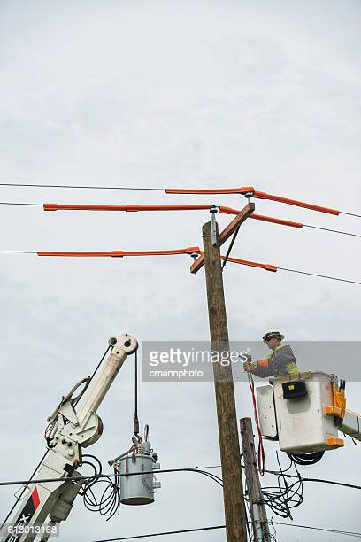 Lineman replacing electrical power transformer on utility pole