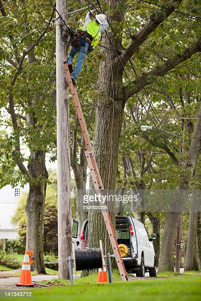 Lineman working on telecommunications wires at a utility pole