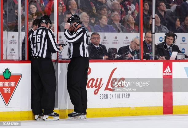 Linemen Michel Cormier and Lonnie Cameron review a coaches challenge for offside by the Philadelphia Flyers on a goal by the Ottawa Senators of the...