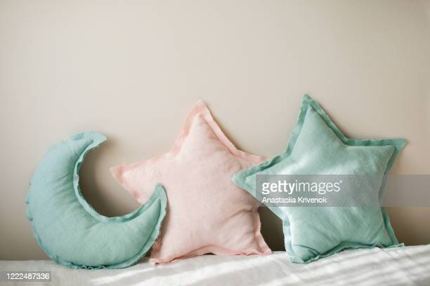 linen blue and pink moon and star pillows toy on light bedding over beige background. decorative baby cushions on nursery. - cushion stock pictures, royalty-free photos & images