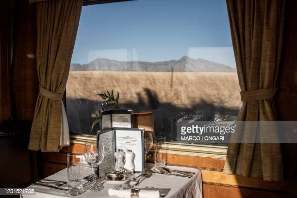 Linen, crystals and silverware are seen in the dining car as Blue Train approaches the Karoo area on February 25, 2021. - Forty-eight hours to stop...