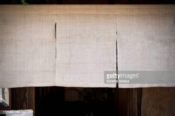 a linen noren japanese curtain still a doorway from street - のれん ストックフォトと画像