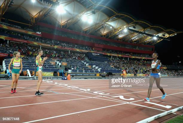 Lineo Chaka of Lesotho is greeted by Madeline Hills of Australia and Celia Sullohern of Australia as she finishes the Women's 10000 metres final...