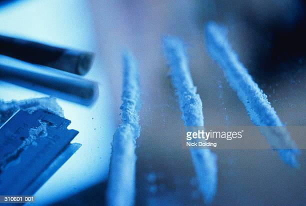 Lines of cocaine, razor blade and rolled paper, close-up, blue wash