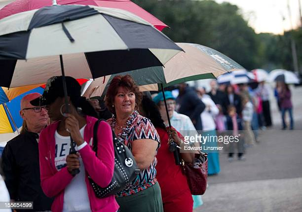 Lines of voters wait in the rain to cast their ballots as the polls open November 6 2012 in St Petersburg Florida The swing state of Florida is a...
