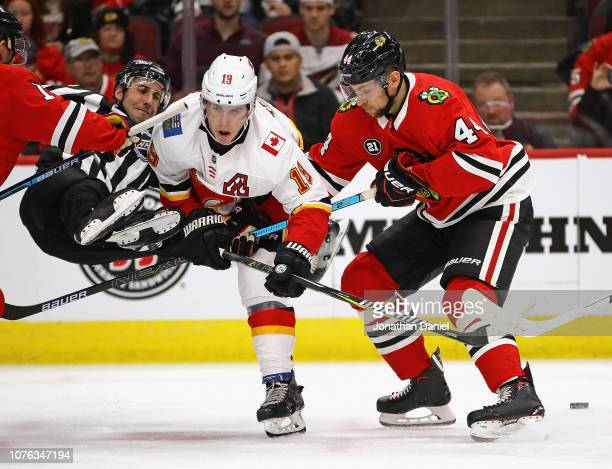 Linesman Andrew Smith slips and falls to the ice after dropping a face off puck between Matthew Tkachuk of the Calgary Flames and Jan Rutta of the...