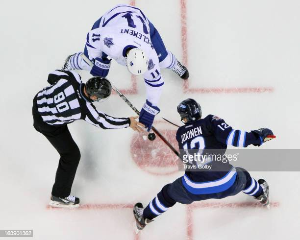 Linesman Andy McElman drops the puck between Jay McClement of the Toronto Maple Leafs and Olli Jokinen of the Winnipeg Jets during a second period...