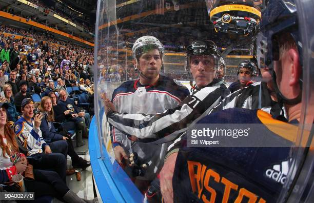 NHL linesman Brad Kovachik clears Josh Anderson of the Columbus Blue Jackets away from Rasmus Ristolainen of the Buffalo Sabres during the second...