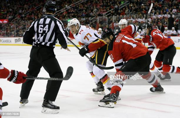 Linesman Brandon Gawryletz drops the puck on a faceoff between Brian Boyle of the New Jersey Devils and Mark Jankowski of the Calgary Flames during...