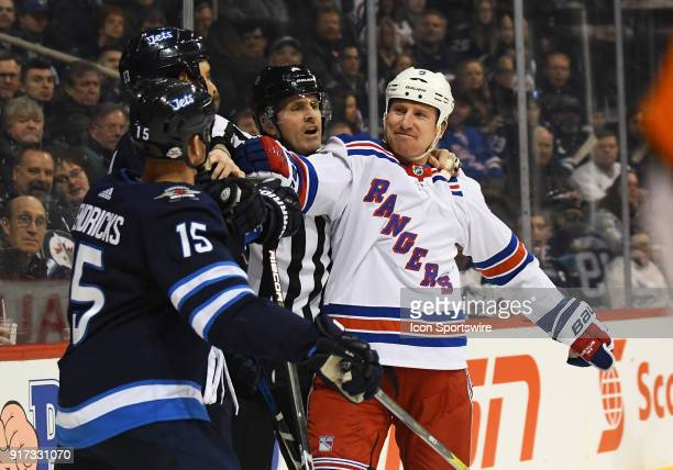 A linesman breaks up a scuffle between Winnipeg Jets Center Matt Hendricks Winnipeg Jets Defenceman Dustin Byfuglien and New York Rangers Left Wing...