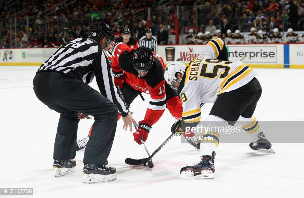 Linesman Brian Mach drops the puck on a faceoff between Brian Boyle of the New Jersey Devils and Tim Schaller of the Boston Bruins during the game at...