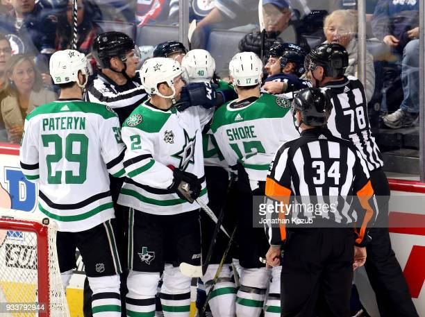 Linesman Brian Murphy and Brian Mach try to separate Winnipeg Jets and Dallas Stars players during a second period scrum at the Bell MTS Place on...