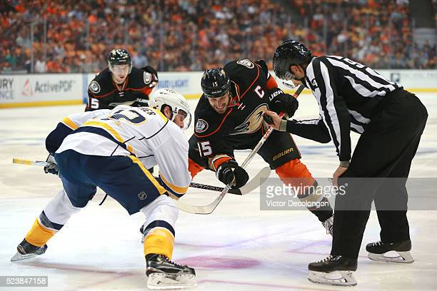 NHL linesman Bryan Pancich looks to drop the puck as Mike Fisher of the Nashville Predators and Ryan Getzlaf of the Anaheim Ducks vie for position...