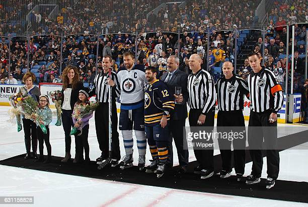 Linesman David Brisebois left is honored for his 1000th NHL game before the game between the Buffalo Sabres and Winnipeg Jets at the KeyBank Center...