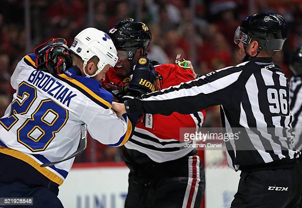 Linesman David Brisebois tries to break up a fight between Kyle Brodziak of the St Louis Blues and Viktor Svedberg of the Chicago Blackhawks in Game...
