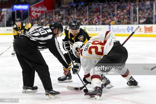 Linesman Dennis Urban drops the puck between Wilkes-Barre/Scranton Penguins left wing Andrew Agozzino and Cleveland Monsters center Justin Scott...
