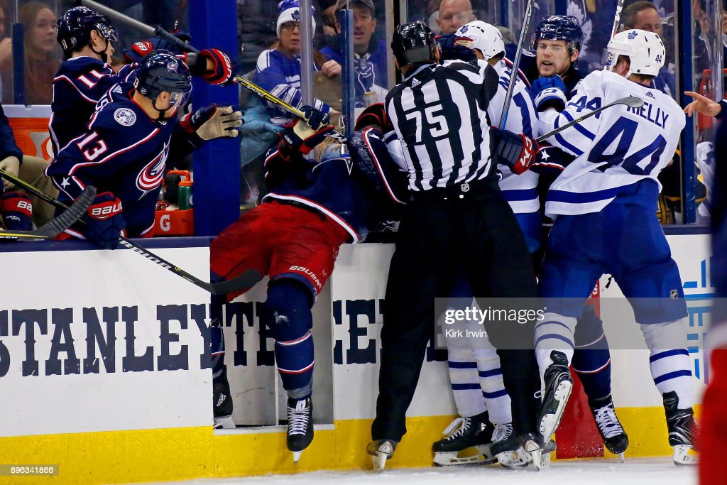 Linesman Derek Amell #75 attempts to pull #15 away from Lukas Sedlak #45 of the Columbus Blue Jackets during the third period on December 20, 2017 at Nationwide Arena in Columbus, Ohio. Columbus defeated Toronto 4-2.