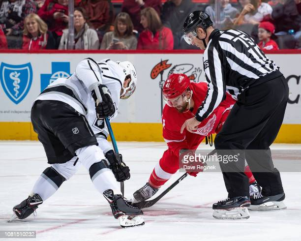 Linesman Derek Amell drops the puck between Luke Glendening of the Detroit Red Wings and Anze Kopitar of the Los Angeles Kings during an NHL game at...