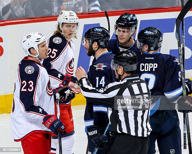 Linesman Derek Amell gets between David Clarkson of the Columbus Blue Jackets and Anthony Peluso of the Winnipeg Jets during a third period exchange...