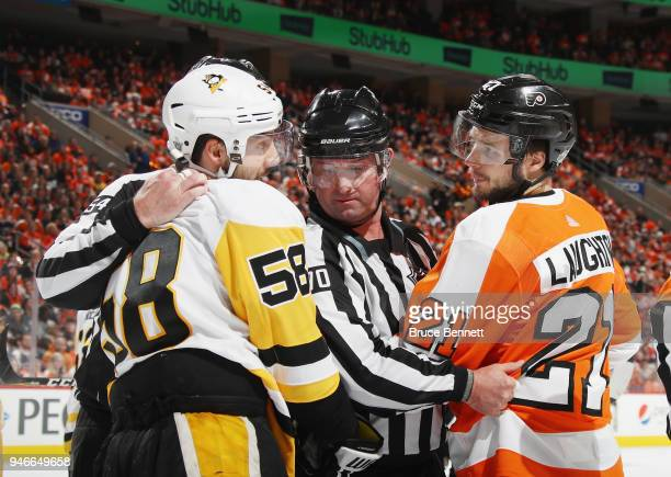 Linesman Derek Nansen gets between Kris Letang of the Pittsburgh Penguins and Scott Laughton of the Philadelphia Flyers during the second period in...