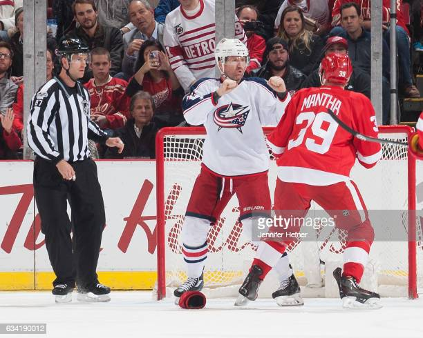 Linesman Devin Berg watches as Scott Hartnell of the Columbus Blue Jackets and Anthony Mantha of the Detroit Red Wings drop the gloves during an NHL...