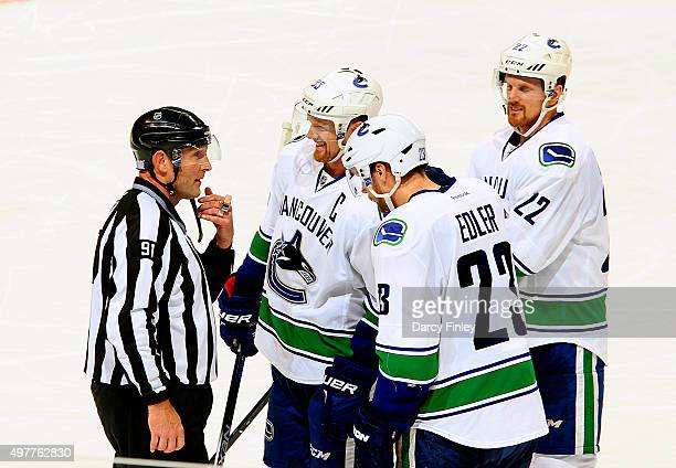 Linesman Don Henderson chats with Henrik Sedin Alexander Edler and Daniel Sedin of the Vancouver Canucks during a second period stoppage in play...