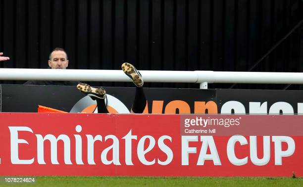 Linesman falls over the advertising boards during the FA Cup Third Round match between Woking and Watford at Kingfield Stadium on January 6 2019 in...