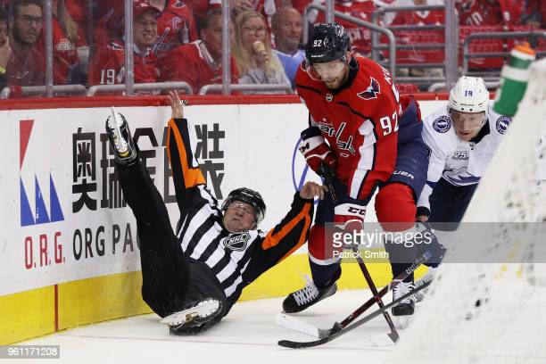 A linesman is upended as Evgeny Kuznetsov of the Washington Capitals and Ondrej Palat of the Tampa Bay Lightning vie for posession in the second...