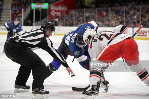 Linesman James Tobias drops the puck between Cleveland Monsters center Zac Dalpe and Grand Rapids Griffins left wing Eric Tangradi during the second...