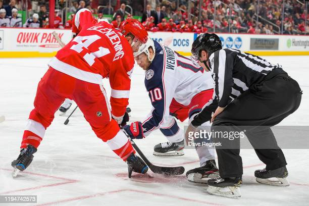 Linesman James Tobias drops the puck between Luke Glendening of the Detroit Red Wings and Alexander Wennberg of the Columbus Blue Jackets during an...