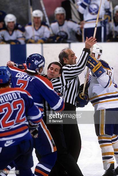 Linesman John D'Amico holds back Craig Ramsay of the Buffalo Sabres as Paul Coffey of the Edmonton Oilers tries to get at him circa 1984 at the...