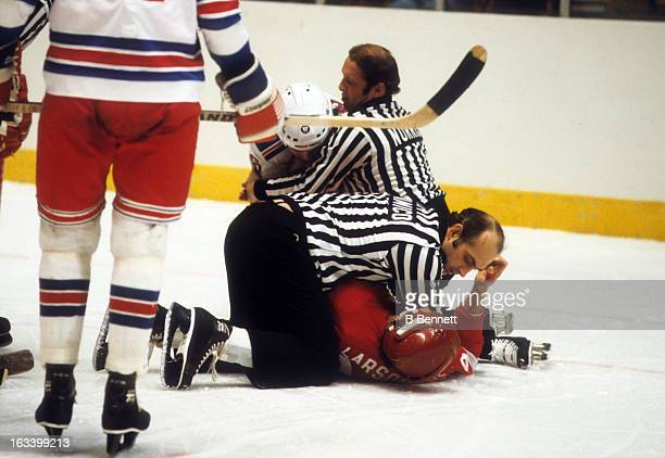 Linesman John D'Amico holds down Reed Larson of the Detroit Red Wings after a fight during an NHL game against the New York Rangers on December 22...