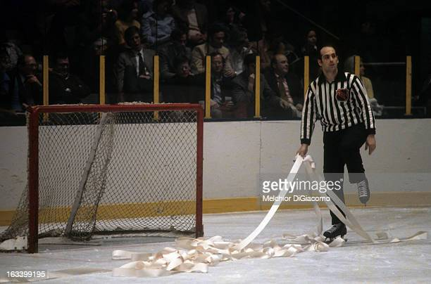 Linesman John D'Amico picks up toilet paper after unruly fans threw it on the ice during an NHL game with the New York Rangers circa 1972 at the...