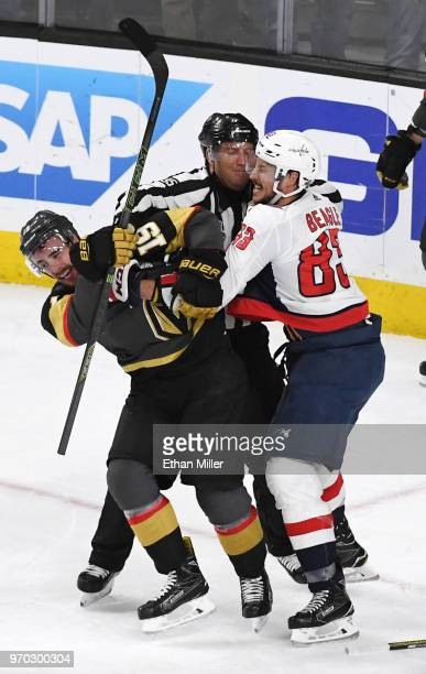 Linesman Jonny Murray tries to break up Reilly Smith of the Vegas Golden Knights and Jay Beagle of the Washington Capitals as they fight after Smith...