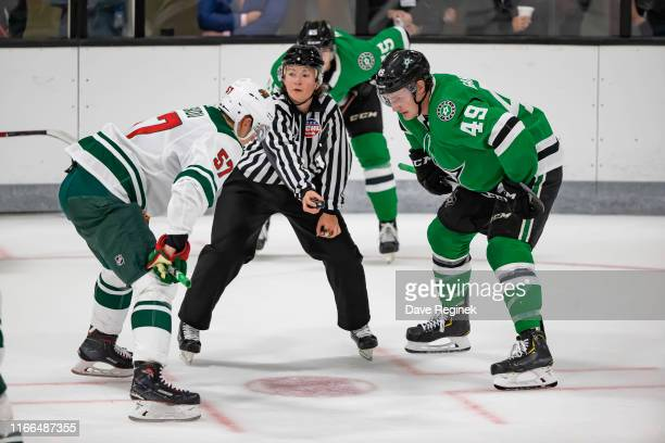 Linesman Kendall Hanley gets ready to drop the puck between Joel Kiviranta of the Dallas Stars and Matvey Guskov of the Minnesota Wild during Day1 of...