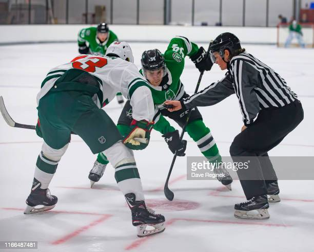 Linesman Kendall Hanley gets ready to drop the puck between Joel Kiviranta of the Dallas Stars and Adam Beckman of the Minnesota Wild during Day1 of...