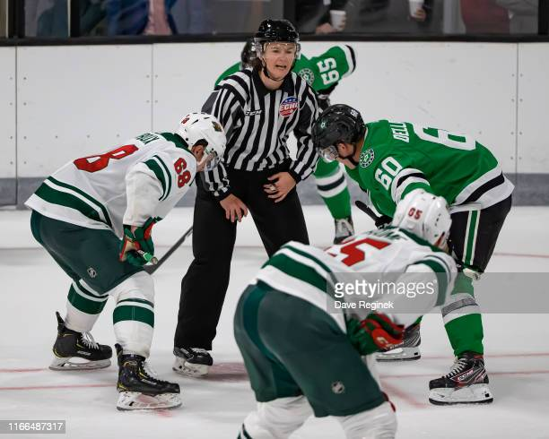 Linesman Kendall Hanley gets ready to drop the puck between Ty Dellandrea of the Dallas Stars and Damien Giroux of the Minnesota Wild during Day1 of...
