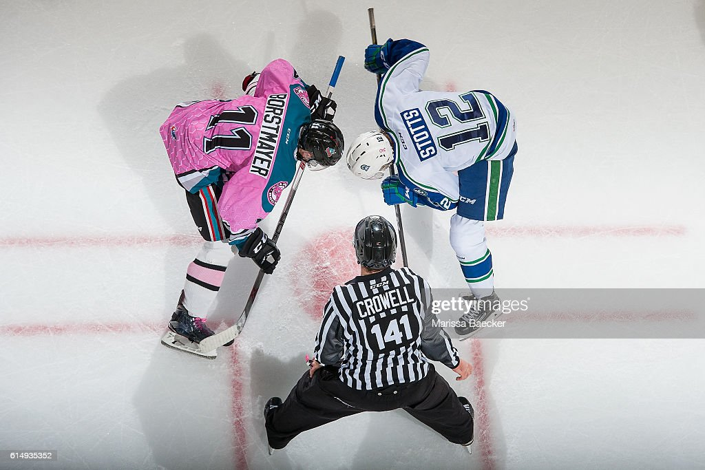 Linesman Kevin Crowell stands at the face-off between Jordan Borstmayer #11 of Kelowna Rockets and Riley Stotts #12 of Swift Current Broncos on October 15, 2016 at Prospera Place in Kelowna, British Columbia, Canada.